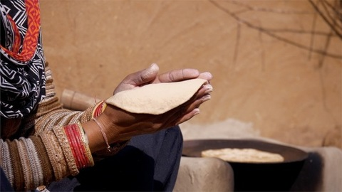 A women making chapati in a rural Indian kitchen