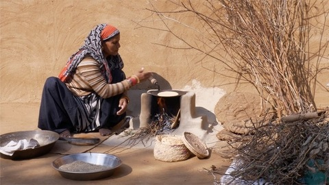 Pan shot of a hardworking Indian woman making roti in chulha / traditional wood fire