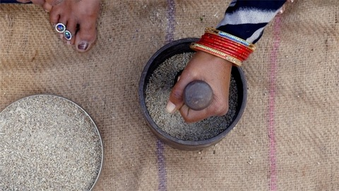 Top view of a woman beating millet / bajra with mortar and pestle (Hamam Dasta)