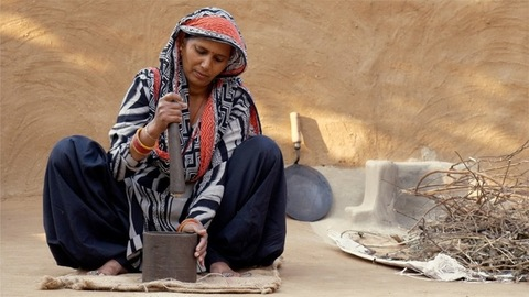 Rural Indian woman pounding spices with mortar and pestle outside her house