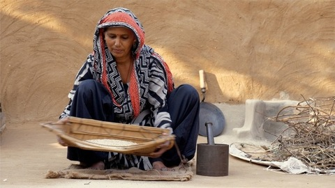 An Indian woman sifting and cleaning rice using traditional technique