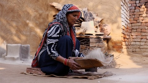 Rural Indian woman sifting rice on the ground outside her home