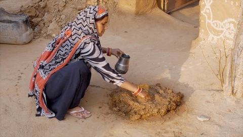 Indian woman preparing a mixture of mud and cow dung