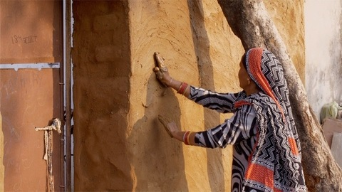 A rural Indian woman repairing house wall with a mixture of mud and cow dung