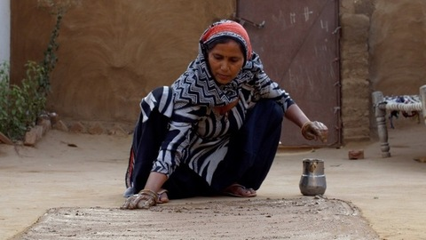 Woman preparing mud floor of her home using cow dung and water