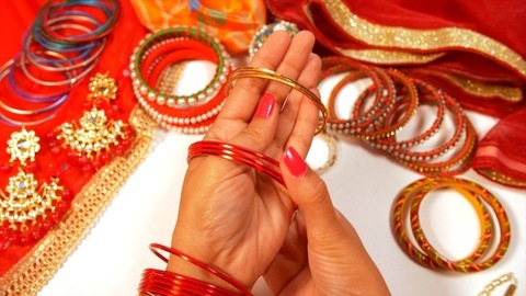 A lady wearing red bangles while getting ready to go out