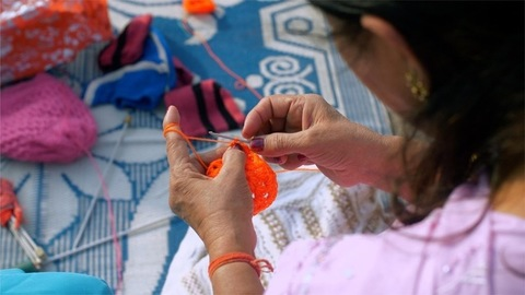 Middle-aged woman knitting woolen clothes using orange yarn and crochet hook