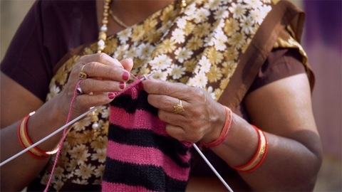 Closeup of woman hands knitting a woolen sweater from the knitting yarn - home hobby