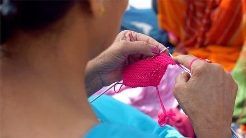Closeup shot of an elderly woman making knitwears using a pink colored yarn