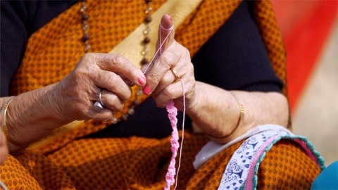 An elderly Indian lady knitting woolen clothes with the help of a crochet hook