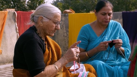 Shot of two old Indian women sitting on the terrace and knitting pink and black colored woolen clothes-Winter Knitwear