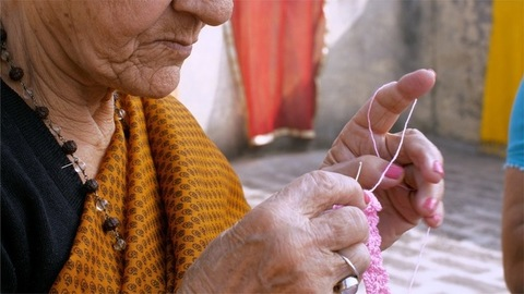An elderly Indian lady in glass spectacles knitting with the help of a crochet hook