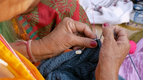 Closeup shot of an Indian old woman knitting woolen clothes using blue wool