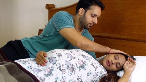 Happy husband taking care of her beautiful pregnant wife while she is sleeping