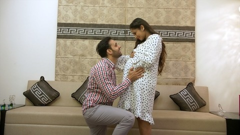 Expecting Indian father kneels down to kiss his pregnant wife's baby bump - lifestyle concept