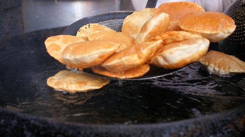 Close shot of hands of a cook taking out fresh puris from the hot oil served with savory curry