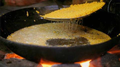 High angle shot of hands preparing sweet Boondi in a big Kadhai - food concept