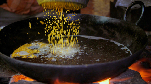 Indian cook working with hot oil in kadhai and preparing sweets for a party