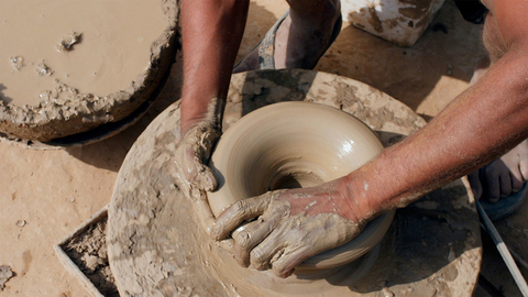 Close up of a potter giving different shapes to the mud clay on a potter's wheel