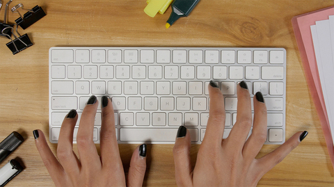 A girl busy working and typing on the keyboard in her office cabin