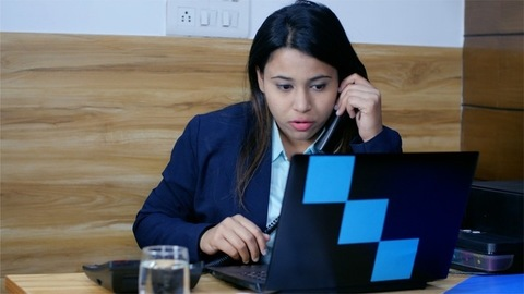 Indian business women (female boss) speaking on phone while working on her laptop