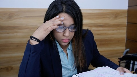 A tensed Indian girl searches important document in her office file