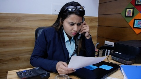 Young Indian female entrepreneur making a phone call and discussing a proposal