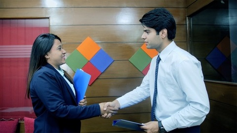A formal office meeting between Indian male and female colleague, exchanging files and shaking hands