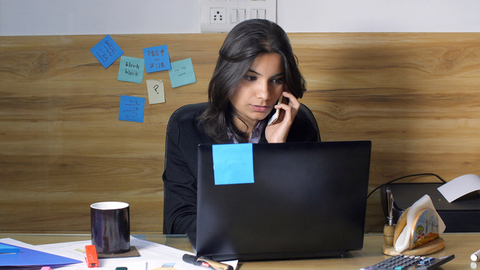 A busy Indian girl frustrated from work talking on phone