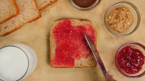 Spreading strawberry jam with a butter knife on a slice of tasty brown bread - popular breakfast