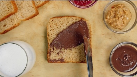 Various breakfast items like milk glass, peanut butter, chocolate spread, and bread