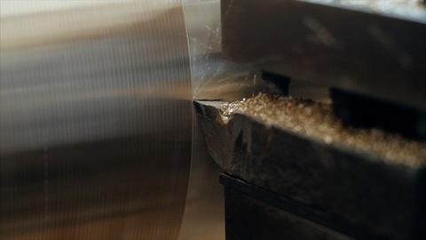 Closeup shot of a lathe machine giving shape to the metal
