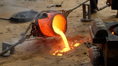 Workers pouring smelted bronze metal into the sand
