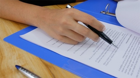 Business man reading the legal contract before signing it
