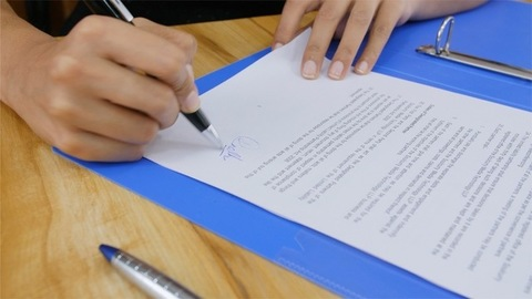 Shot of a business man / woman signing the documents / business proposal / legal contract