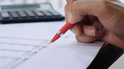 Shot of businesswomen checking the financial statement with a red coloured pen