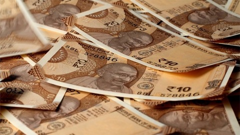 Indian Currency of Rupee 10 notes falling on a table