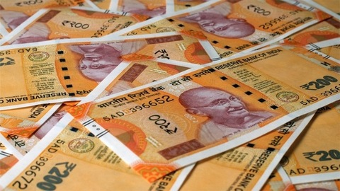 New Indian currency of 200 rupee notes falling on a currency heap