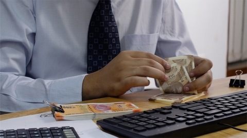 A banker counting Indian currency notes and making entry in his computer