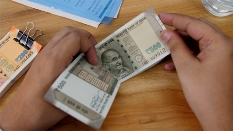Accountant counting rupees 500 Indian currency notes