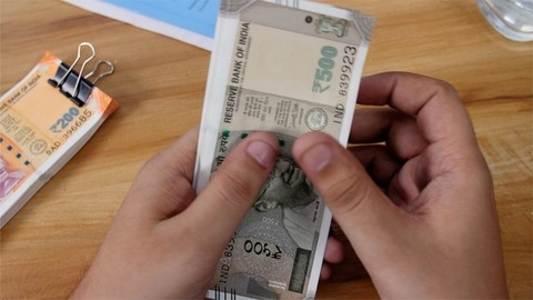 Accountant counts 500 rupees Indian currency