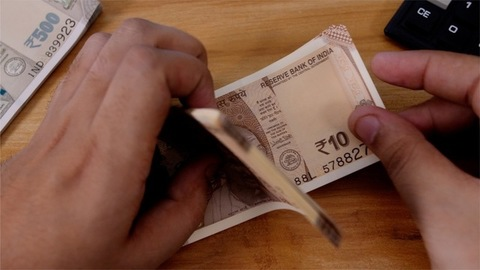 Shot of a banker / bank cashier counting Indian currency Rupee ten notes