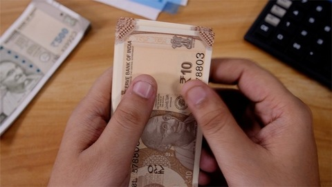 Closeup shot of an accountant counting 10 rupees Indian currency
