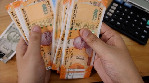 A finance company employee counts Indian currency Rupee 200 notes