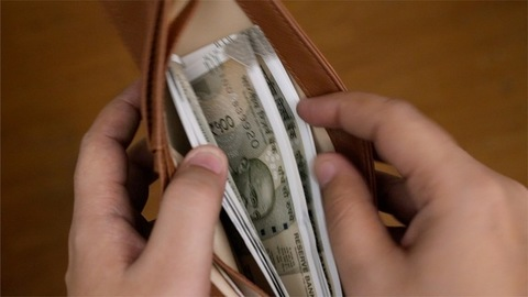 A boy takes out money from his wallet and hands it over to another person