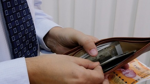 Closeup shot of man taking out Indian currency from his wallet and handing it over