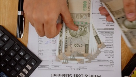 Finance manager of a company counting Rs 500 Indian currency bank notes