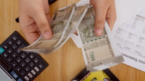 Shot of a man taking out Indian currency from envelope, counting and keeping it back in the envelope