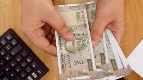 Bank manager / cashier counts and checks the Indian currency - Rupee 500 notes