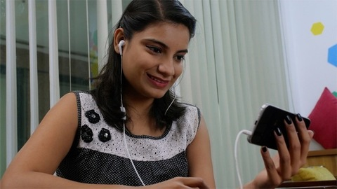Young Indian girl with bright face video chatting with a friend on her smartphone